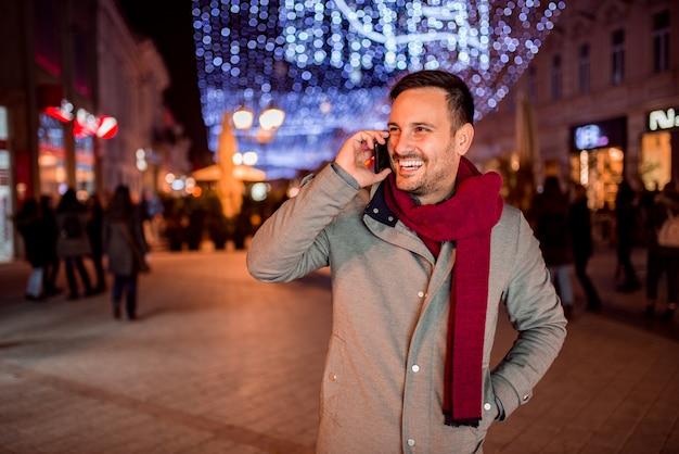 ハンサムな男が飾られた街で夜に携帯電話で話しています。