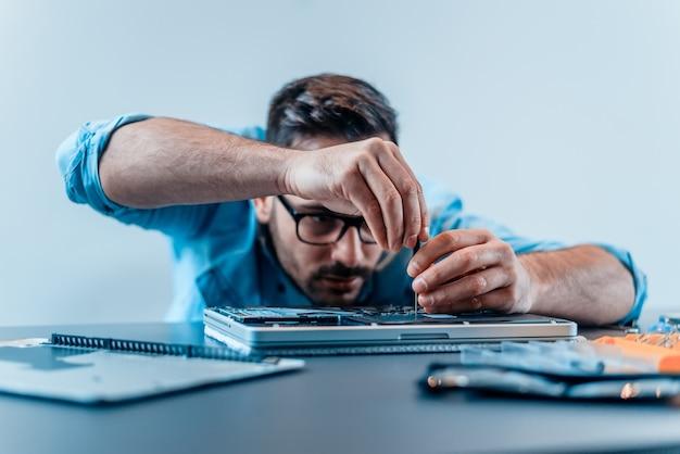 Сосредоточенный инженер разбирает ноутбук с помощью отвертки.