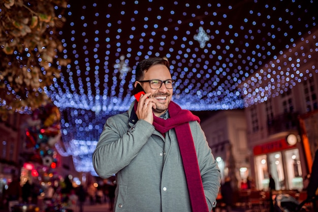 冬の街で電話で話しているハンサムな男は。