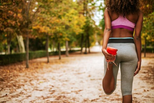 Вид сзади женщины растяжения перед бегом. фитнес и образ жизни концепция.