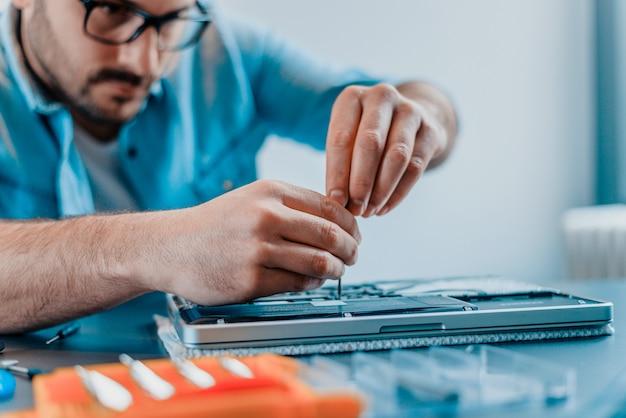 エンジニアはノートパソコンをドライバーで修理します。クローズアップ。