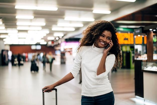 電話で話して、トロリーバッグを持つ空港で若い女性。