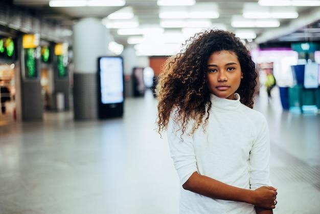 ゴージャスな巻き毛を持つ混血少女の肖像画。カメラを見てください。