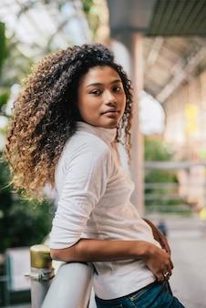巻き毛を持つスタイリッシュな若い女性の肖像画、室内撮影。