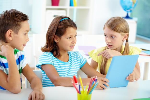 Маленькая девочка разговаривает с ее одноклассником