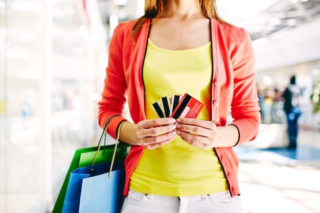 多くのクレジットカードを持つ女性の手のクローズアップ