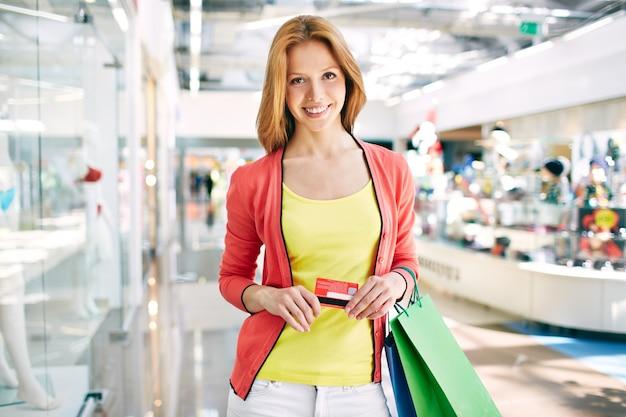 ショッピングバッグやクレジットカードを持つ女性