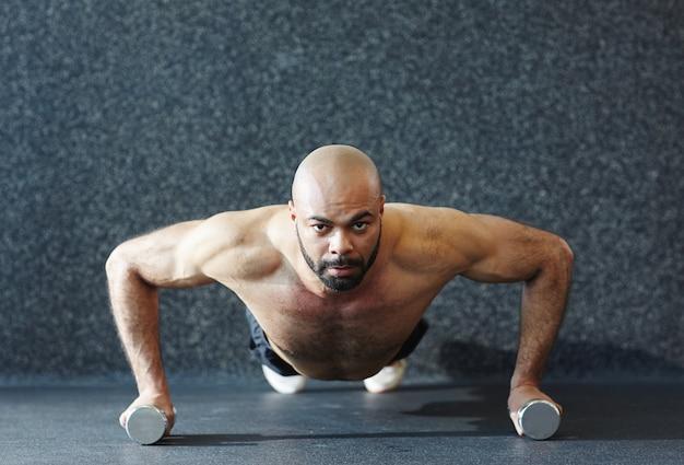 努力でダンベルを押し上げる強い男
