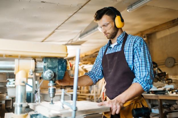 Сверление деревянной доски в мастерской