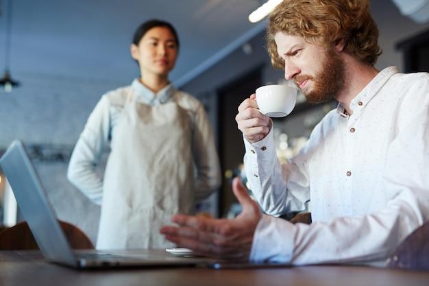 Мужчина пьет кофе или чай во время работы на ноутбуке