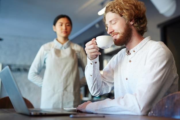 ノートパソコンで作業しながらコーヒーやお茶を飲む男性