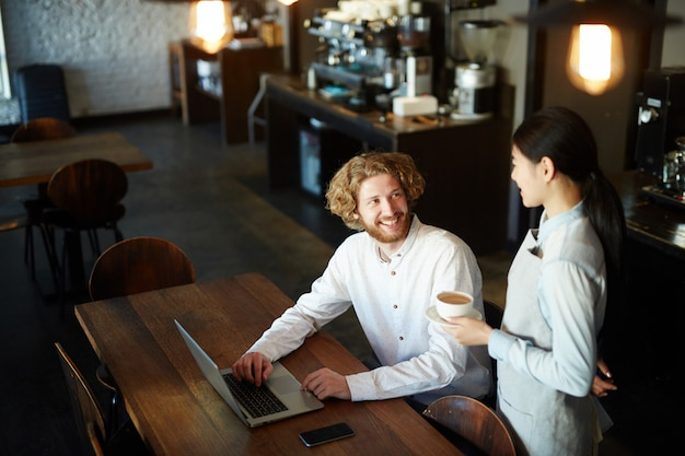 ラップトップに取り組んでいる間レストランでコーヒーを飲む人