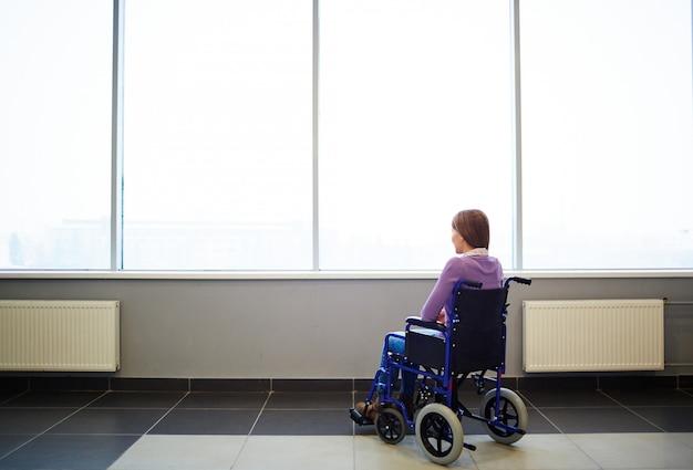Вдумчивый женщина в инвалидной коляске