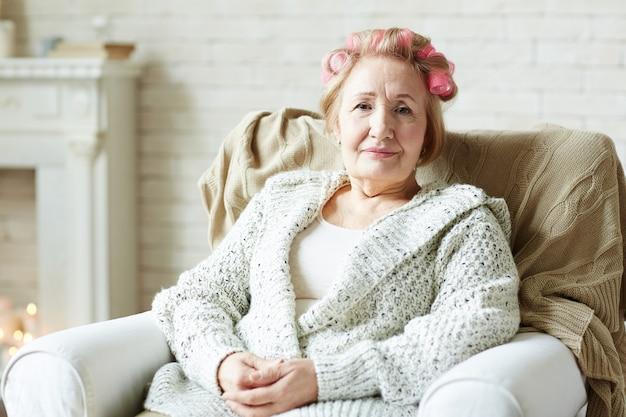 髪のローラを持つ高齢者の女性