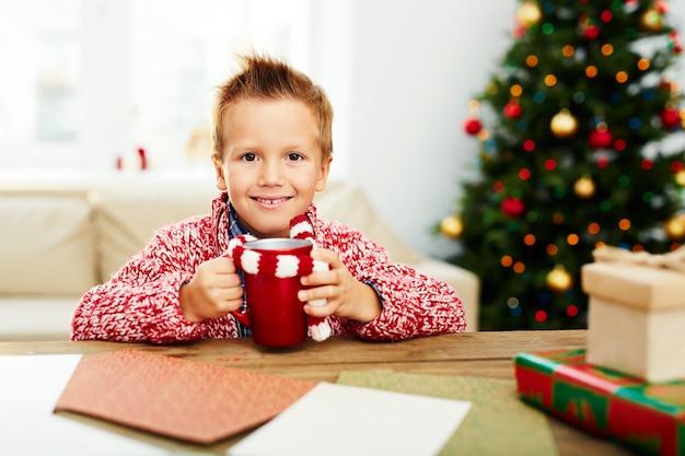 クリスマスに飲み物を持つ少年