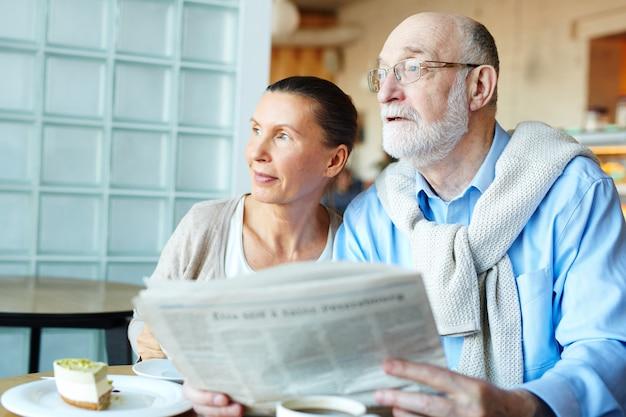 新聞を持つ高齢者