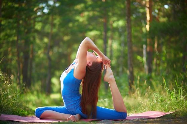 Гибкая женщина делает упражнения на растяжку