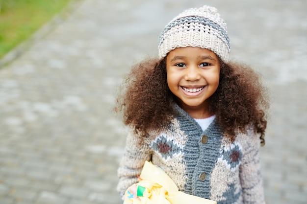 ニットを着ているかわいいアフリカ系アメリカ人の女の子