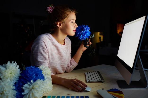 薄暗いスタジオで花のデザイナー