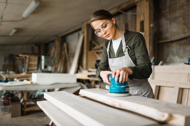 仕事に包まれた女性の木工