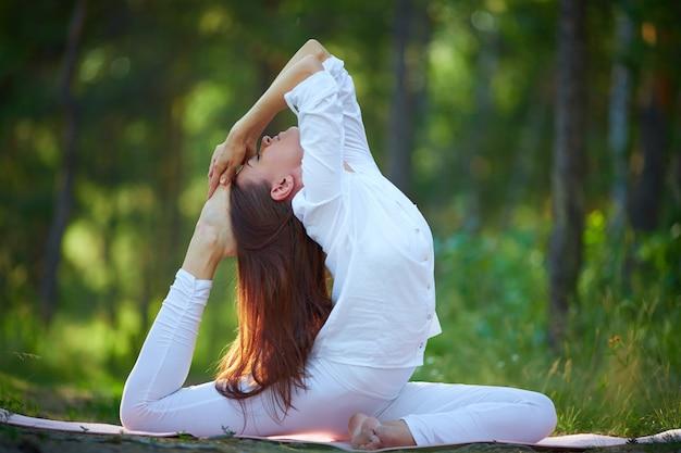 Гибкая женщина делает упражнения йоги