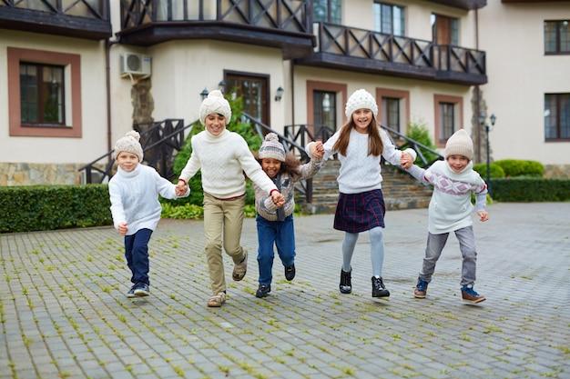 Счастливые дети бегают на улице осенью
