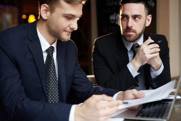 Двое деловых людей рассматривают документы на собрании