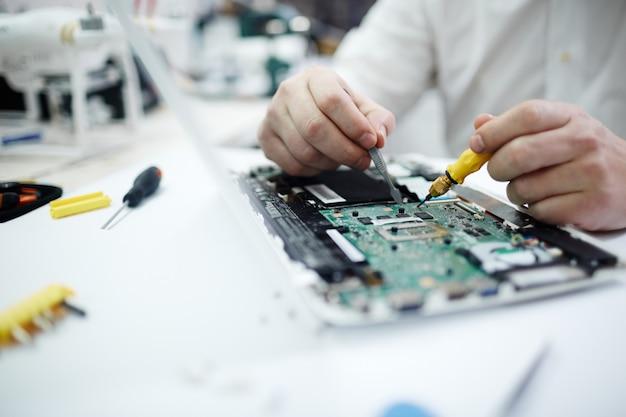 ノートパソコンで回路基板を修復する男