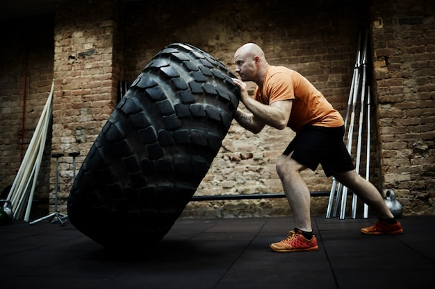 Спортсмен сосредоточен на переворачивании шин