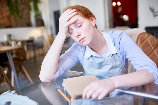 Измученная официантка, страдающая от головной боли