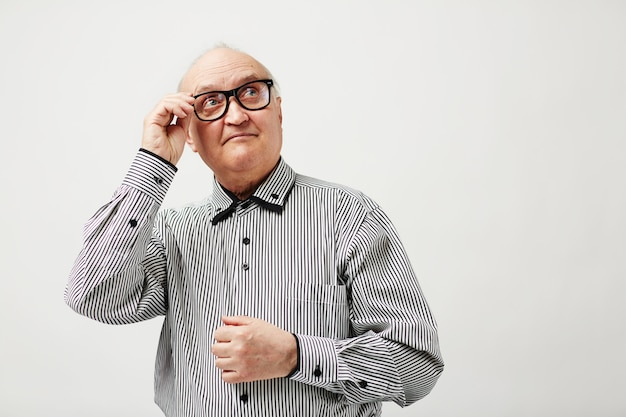 Задумчивый пожилой мужчина в очках