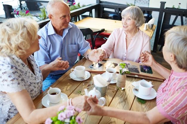 Пожилые люди держатся за руки в кафе