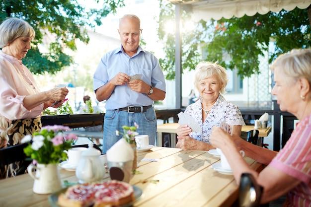 Пожилые люди играют в карты в кафе