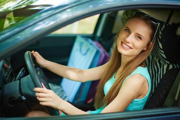 Молодая женщина за рулем своего автомобиля