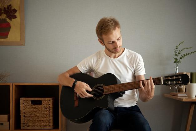 自宅でギターを弾く