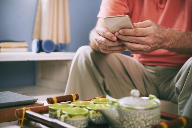 お茶を飲みながらスマートフォンを使用する