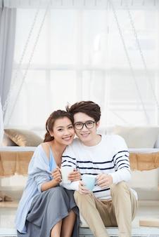Веселая молодая азиатская пара, наслаждаясь кофе
