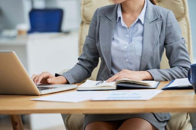 ビジネススーツの机に座って、ラップトップに取り組んで認識できない女性