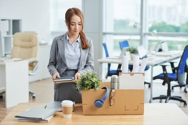 段ボール箱に所持品を持つオフィスでデッキに立っているアジアの女性