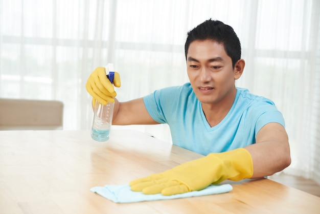 テーブルを噴霧し、自宅で布でクリーニングゴム手袋でアジア人