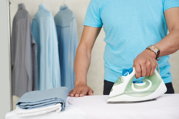 Неузнаваемый мужчина гладит рубашки и стирает дома