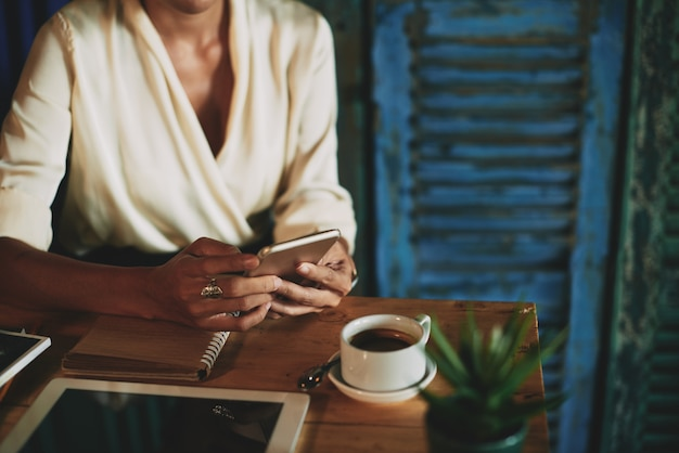 До неузнаваемости женщина сидит в кафе с чашкой кофе и с помощью смартфона
