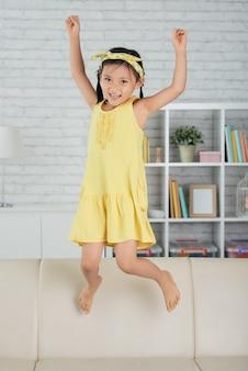 自宅のソファーにジャンプして笑っている若いアジアの女の子