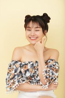 Смеется молодая китайская девушка с закрытыми глазами, в голом плече позирует в студии