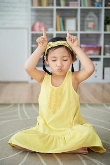 Маленькая азиатская девушка сидит на полу у себя дома и делает коровы рога жест