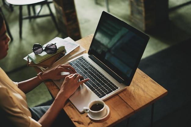 До неузнаваемости азиатская женщина сидит в кафе и работает на ноутбуке