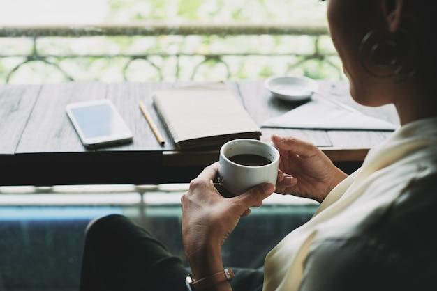 バルコニーに座って一杯のコーヒーを保持している認識できない女性のトップショット