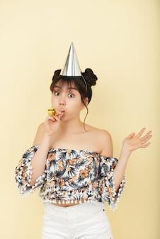 Молодая азиатская женщина представляя в студии в шляпе партии и с шумовиком
