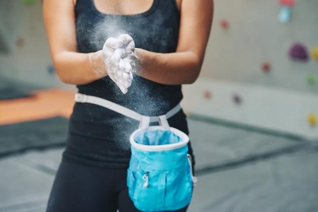 マグネシアで手を粉にする女性をトリミングします。