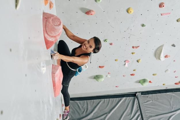 陽気な女性がジムで壁を登る